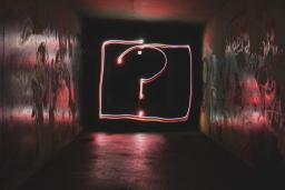 A large, pink graffiti question mark sits at the end of a dark hallway, photo by Emily Morter